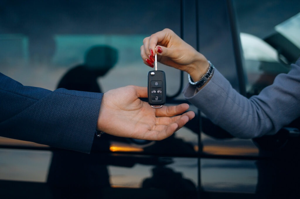 Woman give cars key to man. Hands hold car keys.