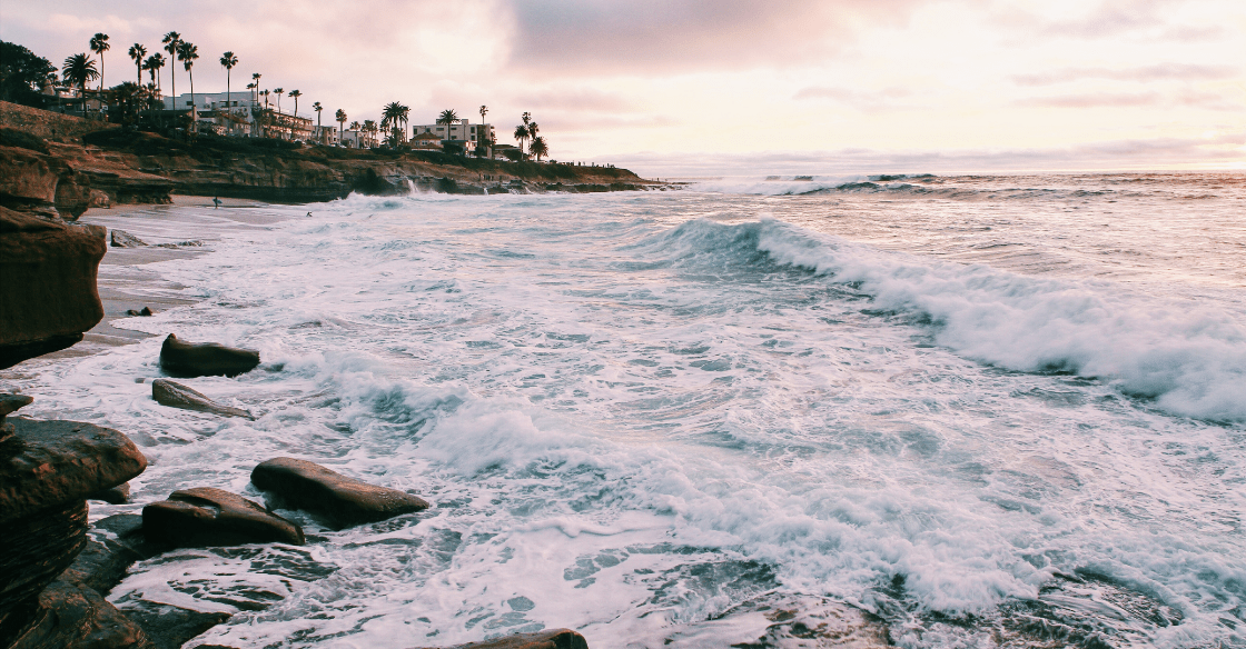 Waves crash on the sand at sunset in San Diego.